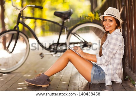 attractive young woman checking her emails outdoors - stock photo