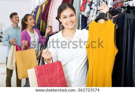 Attractive young woman customers chooses liked things in the boutique