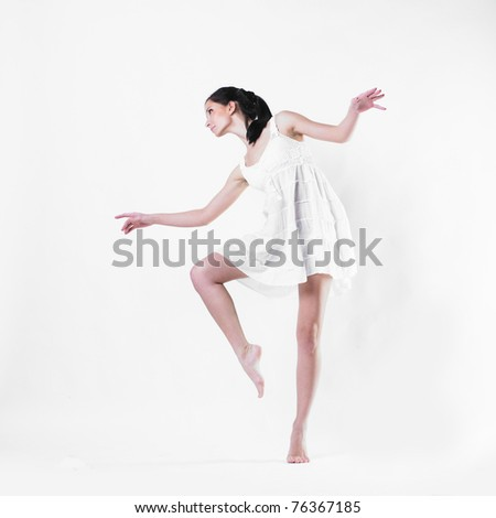 attractive young woman dancing and wearing a light white dress