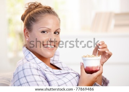 Attractive young woman dieting, eating yoghurt at home.?