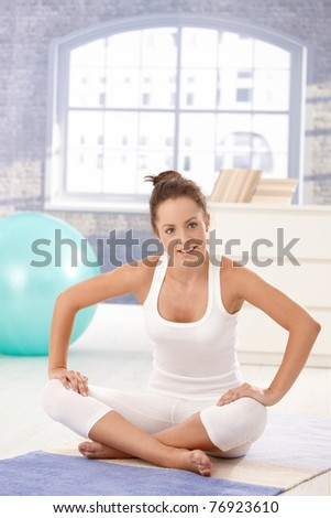 Attractive young woman doing exercises on floor at home, smiling.?