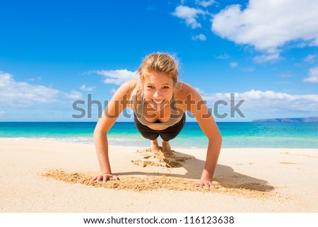 Attractive Young Woman Doing Push Up Exercise on the Beach���  - stock photo