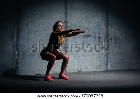 Attractive young woman doing sit ups exercise against concrete wall - stock photo