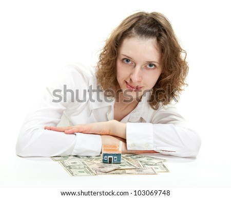 Attractive young woman dreaming of her own house; young woman sitting at the table with small house model and dollar banknotes - stock photo