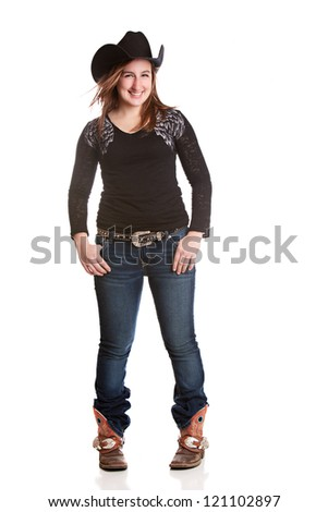 Attractive young woman dressed in a cowboy hat, jeans, and boots with spurs.  Isolated on white.