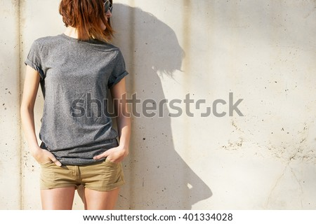 attractive young woman dressed in a gray blank t-shirt posing against a background of a concrete wall in the rays of the setting sun - stock photo