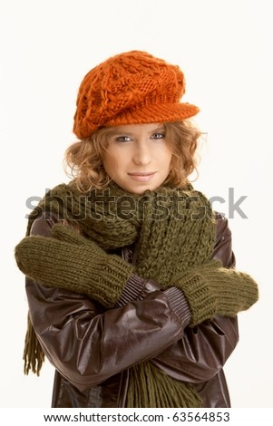 Attractive young woman dressed up warm, arms crossed, freezing.? - stock photo