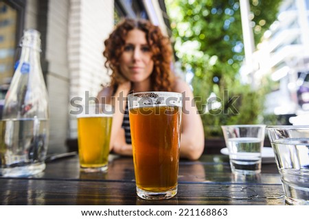 attractive young woman drinking beer at outdoor pub.  focus on glass of beer.