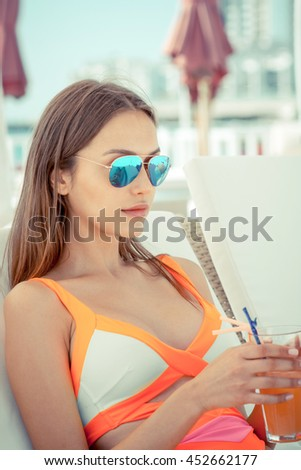 attractive young woman drinking cocktail at summer beach in swimwear