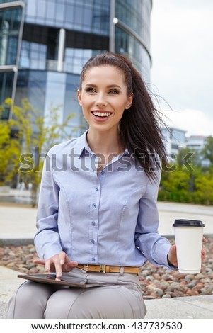 Attractive young woman drinking coffee and reading her touchscreen tablet while standing outside a commercial building