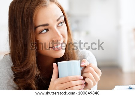 attractive young woman drinking coffee at home - stock photo