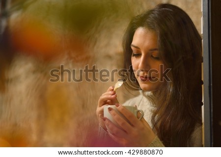 attractive young woman drinking coffee behind a window