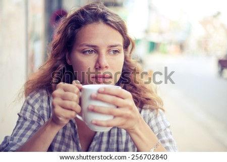 attractive young woman drinking tea in a street cafe. Image with retro toning - stock photo