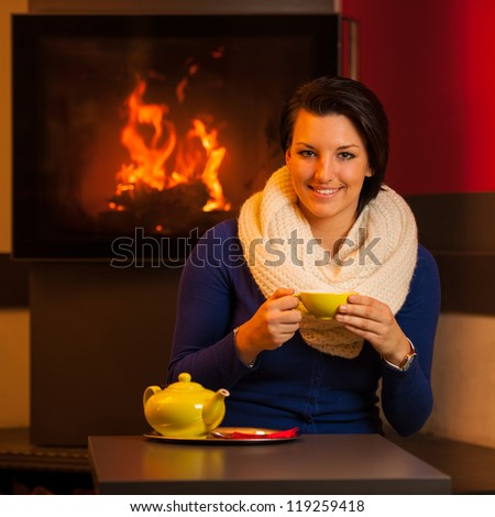 Attractive young woman drinks tea in a warm room near fireplace with teapot on a table - stock photo