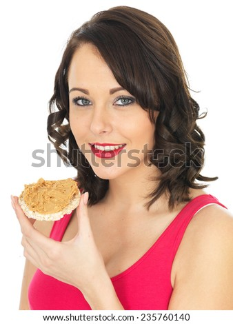 Attractive Young Woman Eating a Cracker with Peanut Butter Spread - stock photo