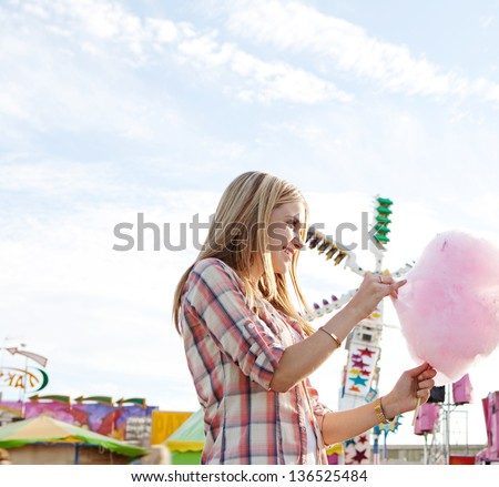 Attractive young woman eating a pink cotton candy floss sweet wile enjoying a funfair ground with colorful rides and a blue sky, smiling. - stock photo