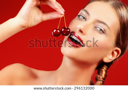 Attractive young woman eating fresh cherry. Sexual lips, red lipstick. Healthy food concept. Cosmetics. Red background. - stock photo