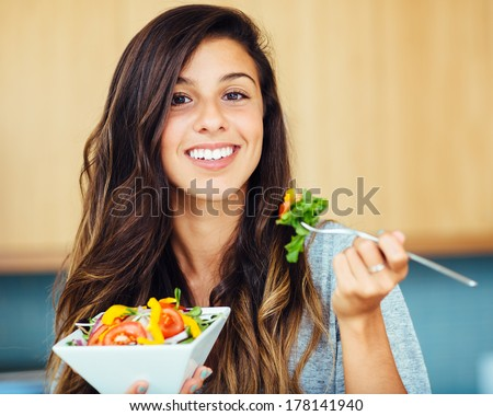 Attractive young woman eating salad - stock photo
