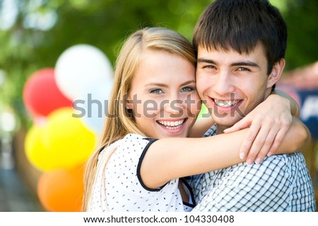 Attractive young woman embracing her handsome boyfrend - stock photo