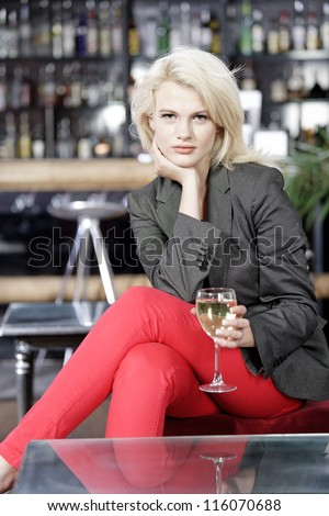 Attractive young woman enjoying a glass of white wine in a wine bar. - stock photo