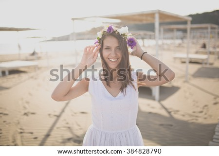 Attractive young woman enjoying her time on the sandy beach.Wearing flower headpiece.Hopeless romantic in white dress and flowers in her hair.Spring/summer lifestyle vacation mood.Vintage effect - stock photo
