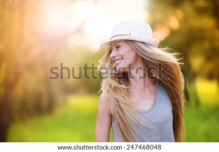 Attractive young woman enjoying her time outside in park with sunset in background. - stock photo