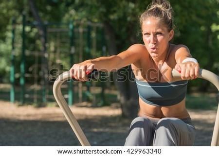 Attractive young woman exercising on rowing machine