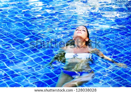 Attractive young woman floating in a swimming pool - stock photo