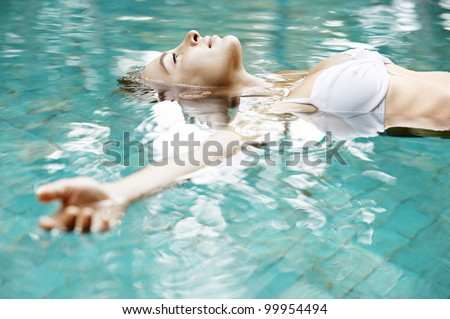 Attractive young woman floating in a swimming pool with her arms outstretched, looking at the sky. - stock photo