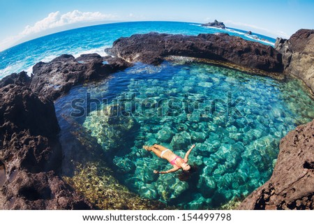 Attractive young woman floating in beautiful ethereal natural pool - stock photo