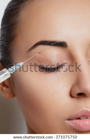Attractive young woman gets cosmetic injection, isolated over white background. Doctors hands making an injection in face. Beauty Treatment. - stock photo