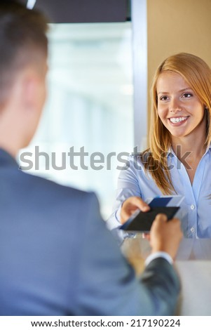 Attractive young woman giving documents to businessman at airport check-in counter - stock photo