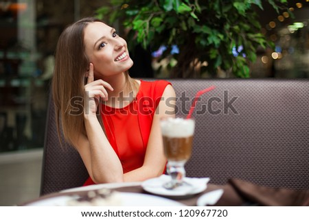 Attractive young woman has a rest in restaurant in front of her on the table tiramisu cake and drink coffee latte in a glass beaker. - stock photo