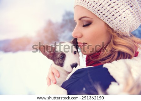 Attractive young woman having fun outside in snow with her dog puppy - stock photo