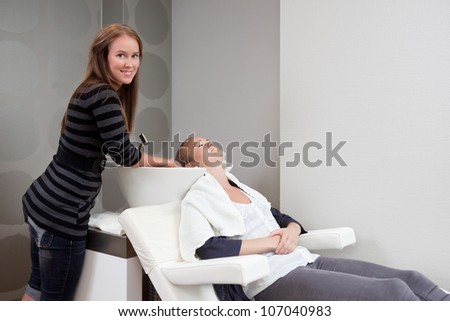 Attractive young woman having her hair washed at beauty salon