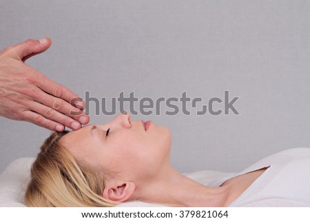 Attractive young woman having reiki healing treatment , alternative  medicine concept. - stock photo