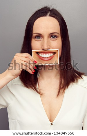 attractive young woman hiding her emotions behind smile - stock photo