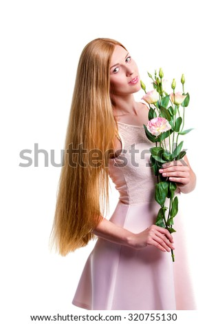 Attractive young woman holding a bunch of flowers while standing against white background in the beige dress