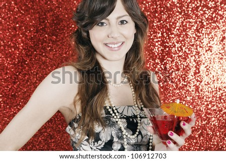 Attractive young woman holding a cocktail glass in a glittering red background at Christmas.