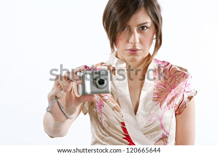 Attractive young woman holding a digital photographic camera while standing isolated against a plain white background, smiling at the camera. - stock photo