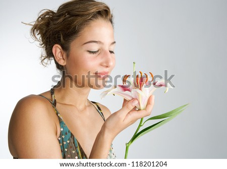 Attractive young woman holding a Japanese lilly flower in her hand, smelling it's perfume against a plain background and smiling.