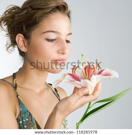 Attractive young woman holding a Japanese lilly flower in her hand, smelling it's perfume against a plain background.