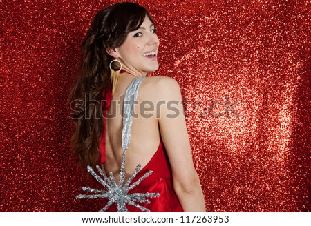 Attractive young woman holding a large christmas star by a ribbon while standing in front of a red glitter background, laughing.