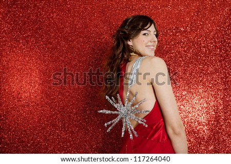 Attractive young woman holding a large christmas star by a ribbon while standing in front of a red glitter background smiling.
