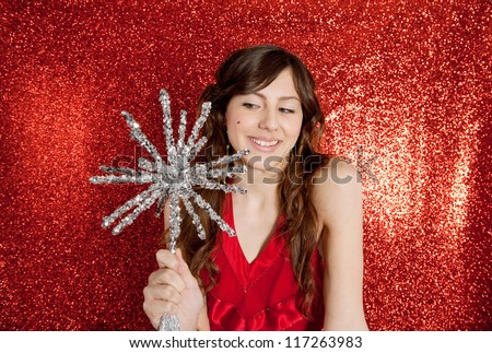 Attractive young woman holding a large christmas star while standing in front of a red glitter background smiling.