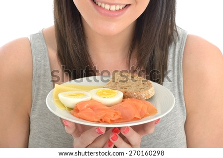 Attractive Young Woman Holding a Typical Healthy Norwegian Breakfast of Eggs Cheese and Smoked Salmon - stock photo