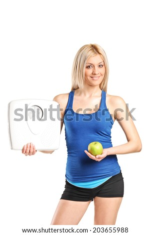 Attractive young woman holding an apple and a weight scale isolated on white background - stock photo