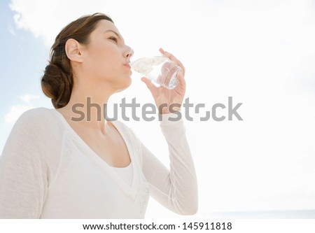 Attractive young woman holding and drinking from a glass of clean water against a sunny sky, hydrating and feeling healthy. - stock photo