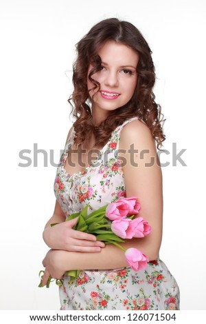Attractive young woman holding beautiful blossom flowers and wearing clothes with floral ornament on Holiday theme - stock photo