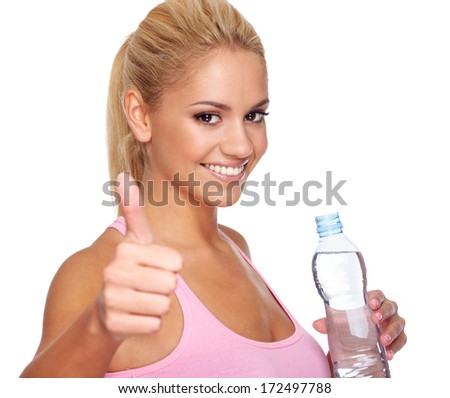 Attractive young woman holding bottle of water and holding thumbs up. Selective focus on face - stock photo